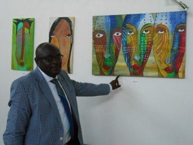 Antoine Goho devant l' une de ses toiles en attraction à la galerie Houkami Guyzagn.