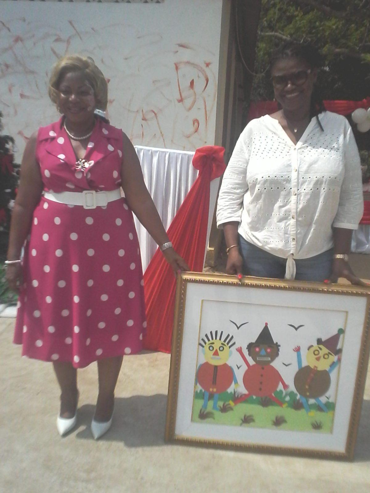 Mme Touré Ouattara Pamatia, donatrice ( en blanc ) recevant des mains de Mme Ouattara Korotoumou, directrice de la pouponnière ( en rose ) un tableau offert par les poupons.